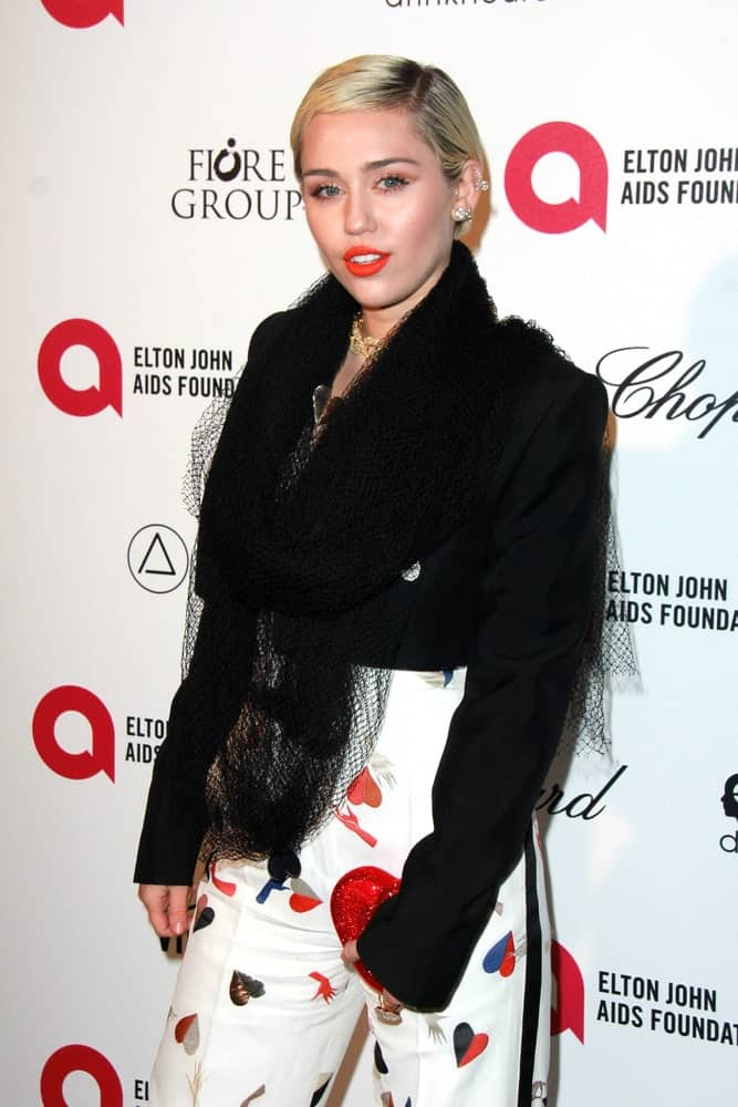 Miley Cyrus wore a smart casual outfit incorporated with a black net scarf at the Elton John Oscar Party 2015 at the City Of West Hollywood Park on February 22, 2015 in West Hollywood, CA. She paired this with bold red lips and a slick blond side-parted short hairstyle.