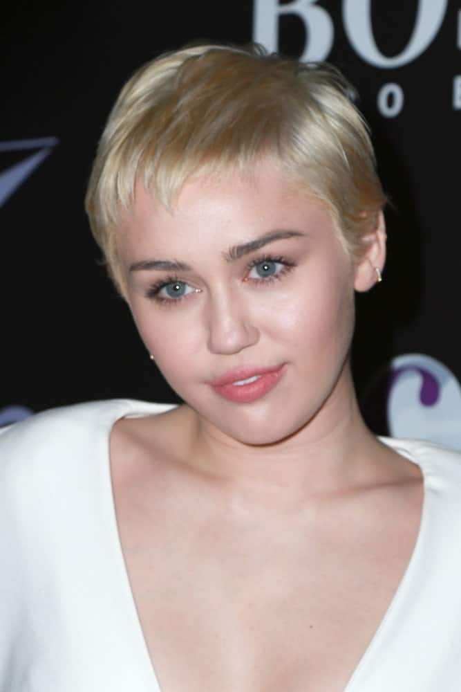 Miley Cyrus paired her white outfit with her platinum blond soft and loose pixie hairstyle with short bangs at the W Magazine`s Shooting Stars Exhibit at the Old May Company Building on January 9, 2015 in Los Angeles, CA.