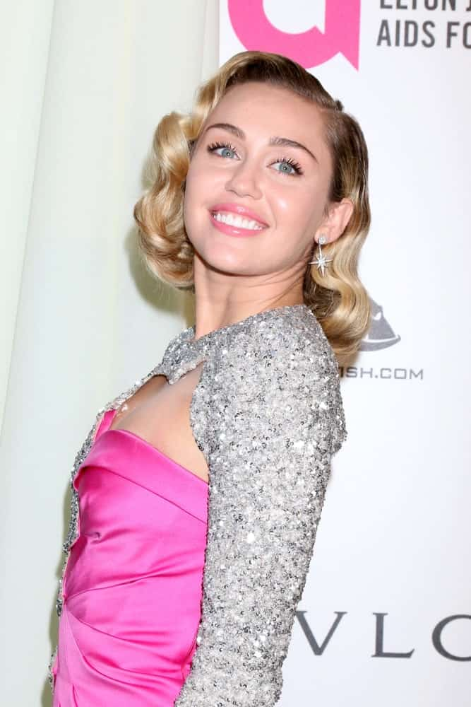 Miley Cyrus attended the 2018 Elton John AIDS Foundation Oscar Viewing Party at the West Hollywood Park on March 4, 2018 in West Hollywood, CA. She went with a vintage look with her classic waves that frame her face and a shiny dress.