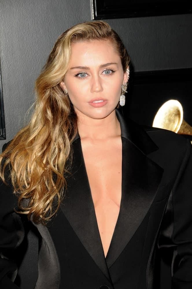 Miley Cyrus was quite stunning in her black coat that she wore at the 61st Grammy Awards at the Staples Center on February 10, 2019 in Los Angeles, CA. She paired this with a stylish side-swept long wavy hair with highlights.