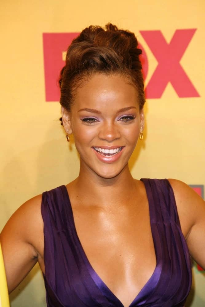 Rihanna wore an elegant and charming purple dress with her detailed upstyle with gorgeous wavy tousle at the top at the 2006 Teen Choice Awards – Press Room at Gibson Amphitheatre on August 20, 2006, in Universal City, CA.