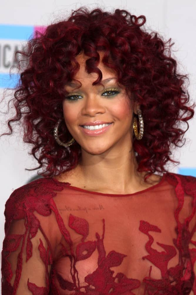 Rihanna attended the 2010 American Music Awards at Nokia Theater on November 21, 2010, in Los Angeles, CA. She paired her stunning red sheer dress with an equally stunning curly red hair left loose and tousled.