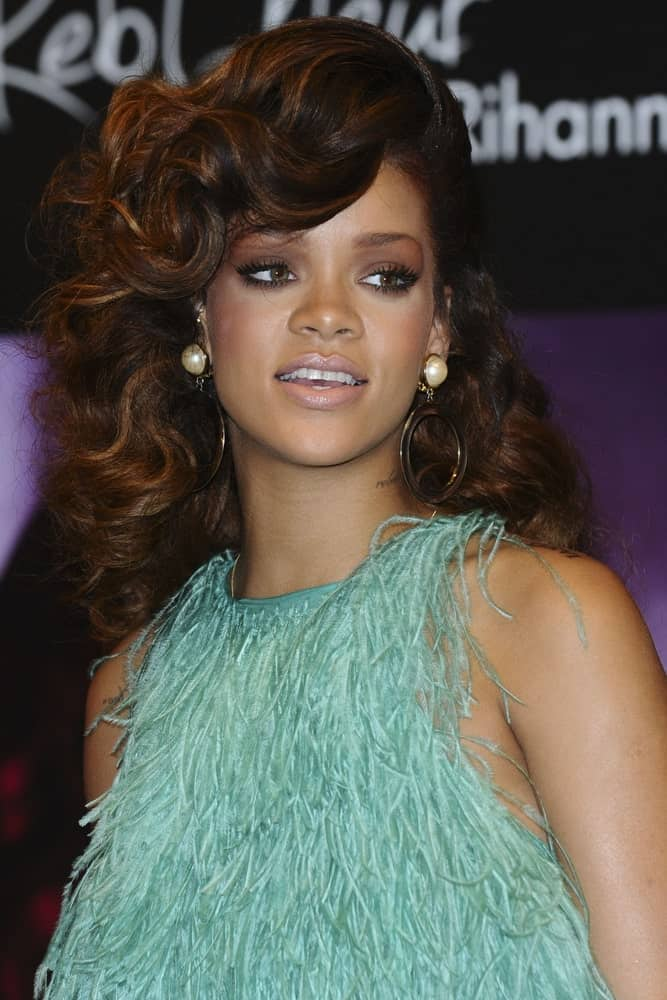 Rihanna went for a vintage look to her feathered green dress and long curly hairstyle with highlights and curly side-swept bangs when she launched her Reb'l fleur perfume at House of Fraser, Oxford St, London on August 22, 2011.
