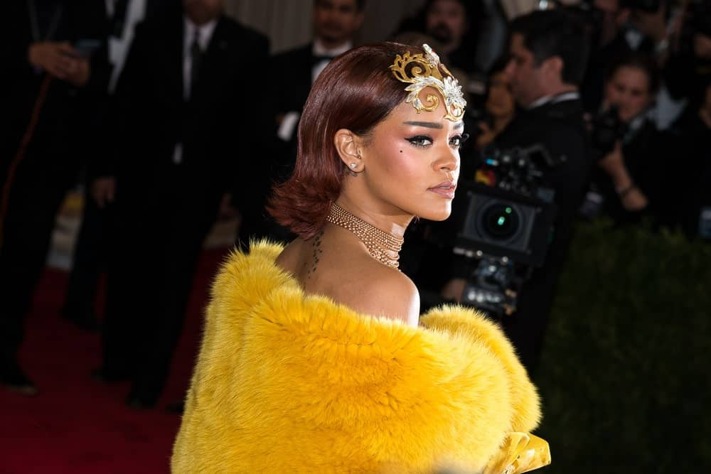 On May 04, 2015, Rihanna attended the 'China: Through The Looking Glass' Costume Institute Gala, held at the Metropolitan Museum of Art in New York City, New York. She wore a vintage yellow dress with fur to match her golden headdress on her slicked-back reddish hairstyle.