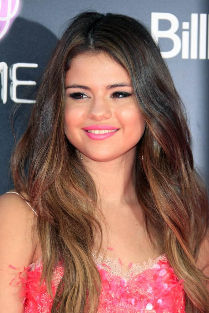 "Selena Gomez was at the ""Katy Perry: Part Of Me"" Premiere at Graumans Chinese Theater on June 26, 2012, in Los Angeles, CA. Her lovely pink detailed dress complemented her long wavy highlights."
