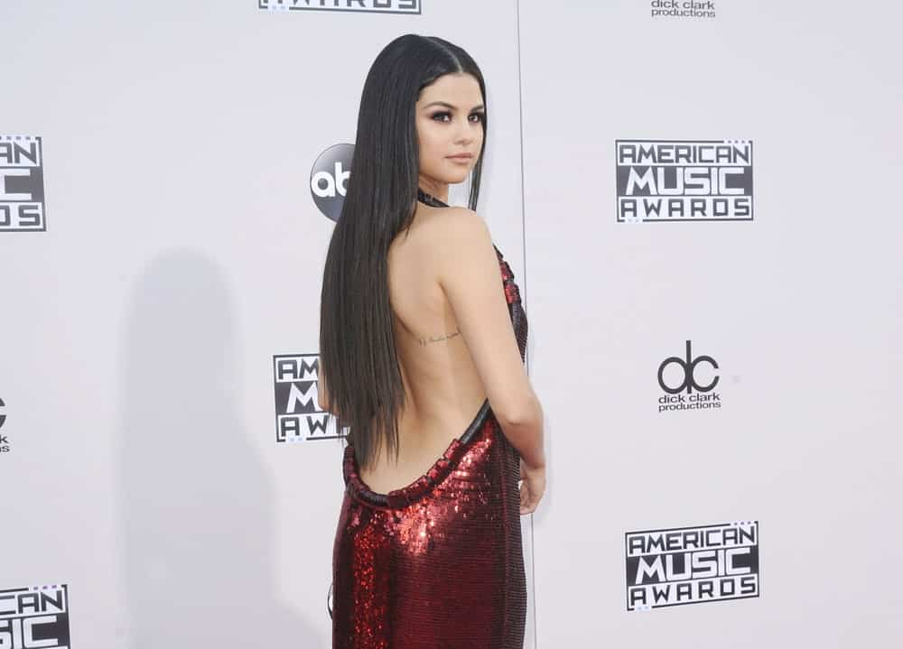 Selena Gomez paired her backless dress with an equally sexy long straight hair loose on her back at the 2015 American Music Awards held at the Microsoft Theater in Los Angeles, USA on November 22, 2015.