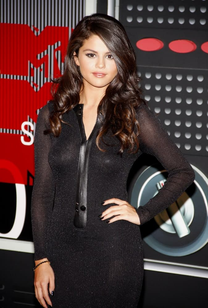 Selena Gomez emphasized her beautiful side-swept curly hairstyle with a simple black dress at the 2015 MTV Video Music Awards held at the Microsoft Theater in Los Angeles, USA on August 30, 2015.