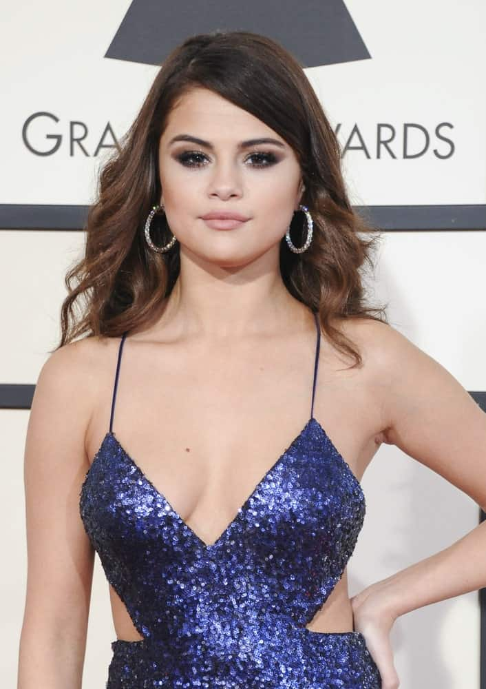 Selena Gomez wore a stunning blue sequined dress with her loose and tousled wavy hair with side-swept bangs at the 58th GRAMMY Awards held at the Staples Center in Los Angeles, USA on February 15, 2016.