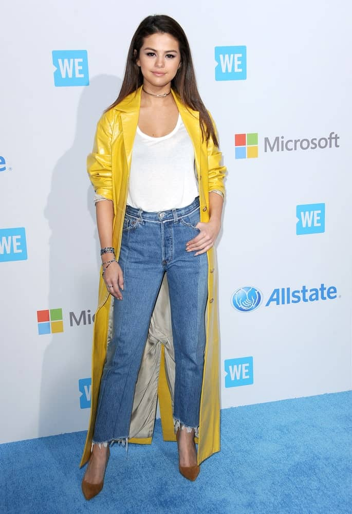 Selena Gomez attended the WE Day California held at the Forum in Inglewood, USA on April 7, 2016. She paired her casual clothes with a yellow trench coat and a long straight dark hairstyle.