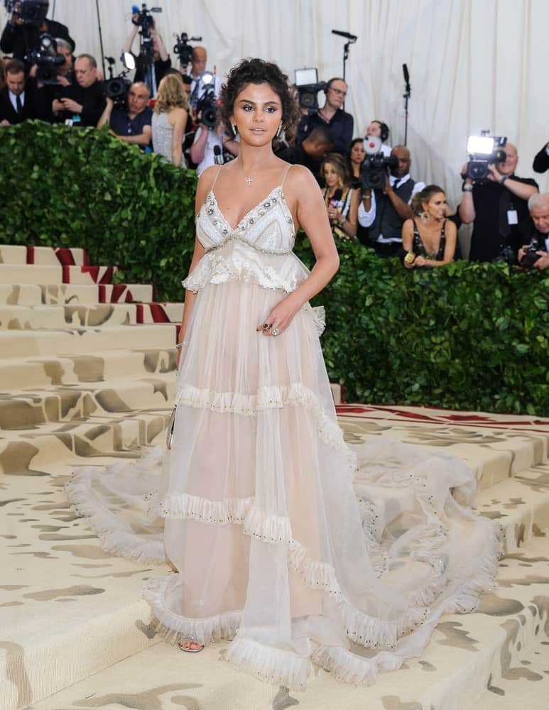 "On May 7, 2018, Selena Gomez was at the Metropolitan Museum of Art Costume Institute Gala: ""Heavenly Bodies: Fashion and the Catholic Imagination. She wore a beautiful long dress and paired it with a short and curly loose half up hairstyle."