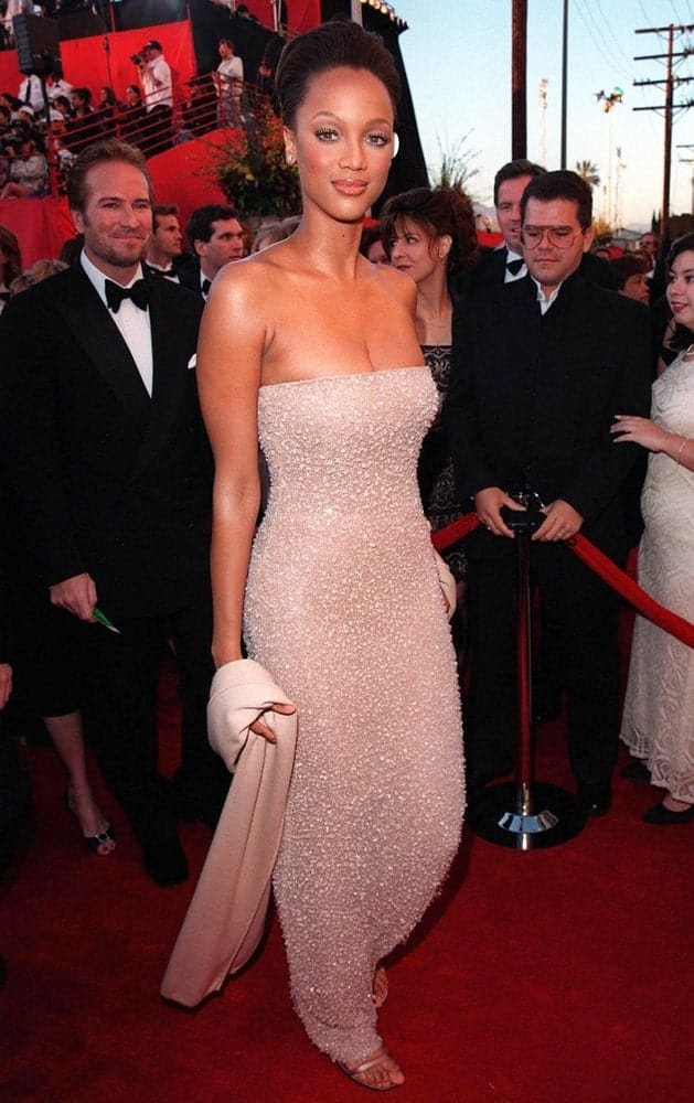 The young supermodel Tyra Banks attended the 70th Academy Awards on March 23, 1998. She wore a lovely champaigne dress that she paired with a classy upstyle.