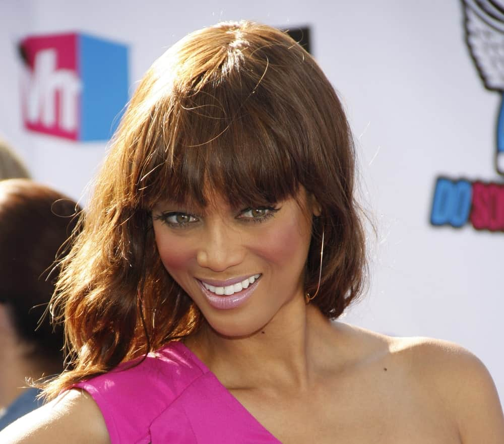 Tyra Banks had a wavy medium-length hair with bangs and a slight tousle at the 2011 VH1 Do Something Awards held at the Palladium Hollywood in Los Angeles, California, United States on August 14, 2011.