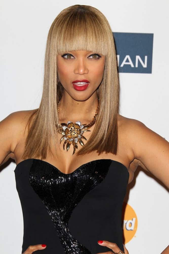 Tyra Banks dyed her hair into a straight sandy blond tone styled with blunt bangs for a Cleopatra look when she arrived at the Clive Davis 2013 Pre-GRAMMY Gala at the Beverly Hilton Hotel on February 9, 2013, in Beverly Hills, CA.
