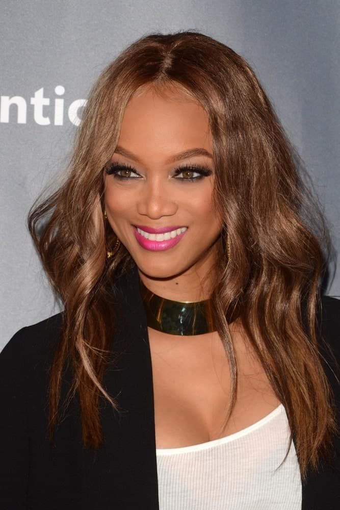 """Tyra Banks's center-parted wavy reddish brown hair complemented her simple smart casual outfit and cheerful make-up at the """"The New Celebrity Apprentice"""" Cast Q&A at Universal Studios on December 9, 2016 in Los Angeles, CA"""