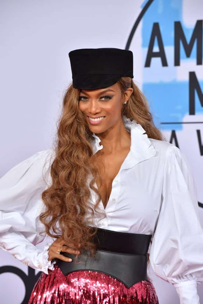 On October 09, 2018, Tyra Banks attended the 2018 American Music Awards at the Microsoft Theatre LA Live. She wore a quirky yet stylish ensemble outfit that paired well with her long and side-swept wavy hairstyle.