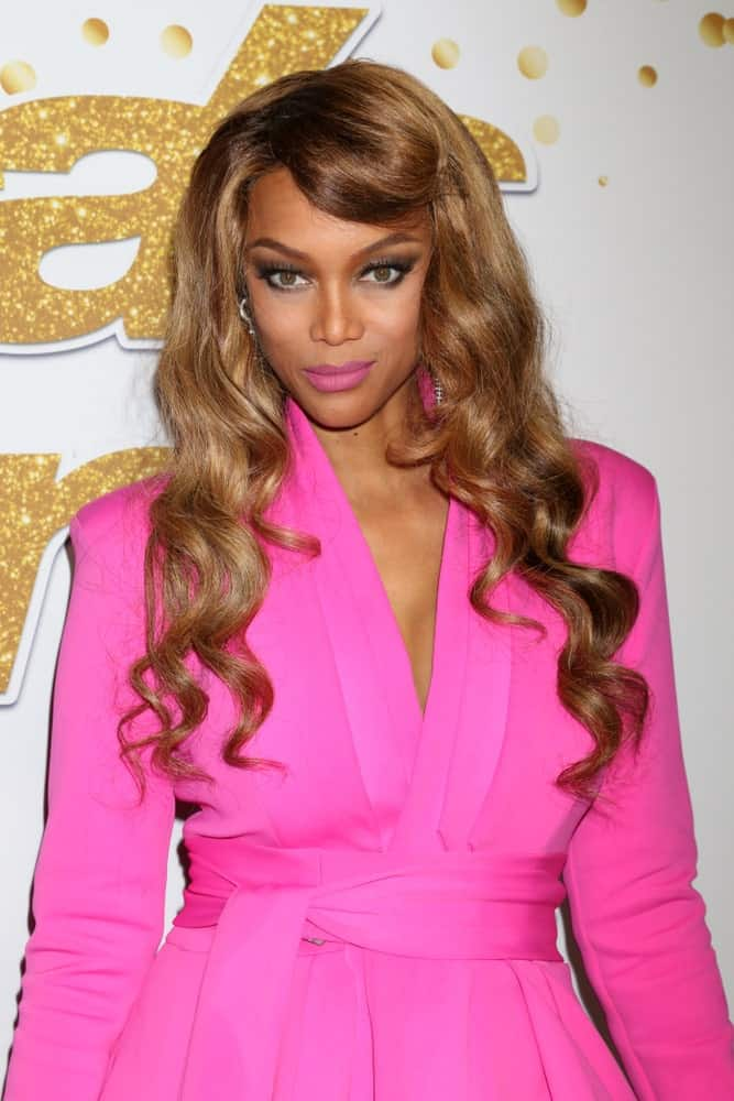 "Tyra Banks's layered and wavy hair was pinned for a half-up look at the ""America's Got Talent"" Live Show Red Carpet at the Dolby Theater on August 28, 2018, in Los Angeles, CA."
