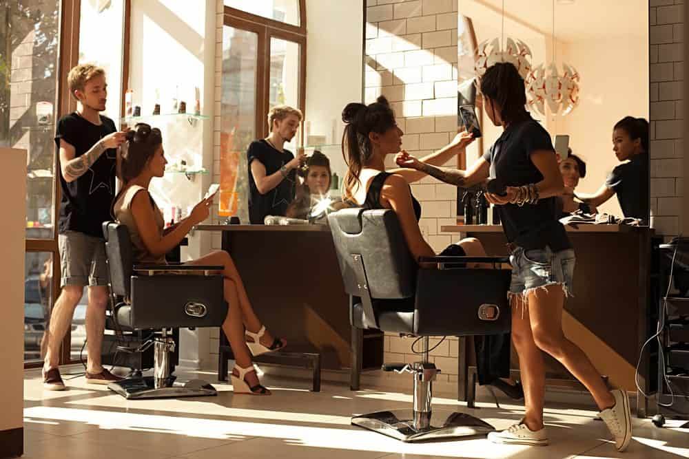 A couple of women having their hair done in a bright and airy salon.
