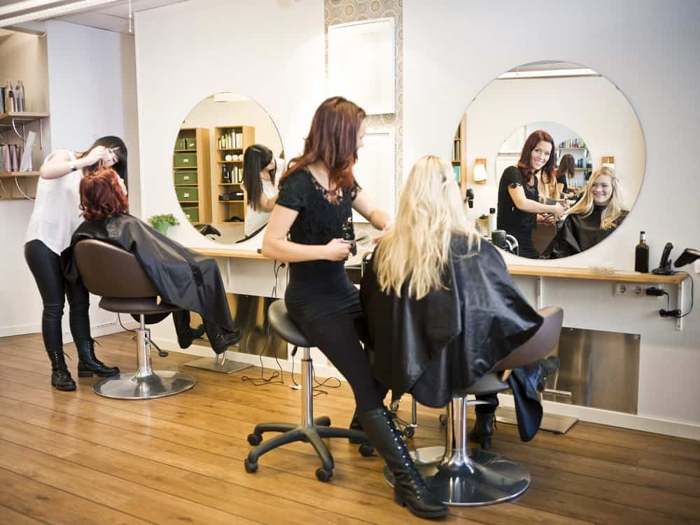 Two women getting a haircut in a beautiful modern salon with wooden flooring.