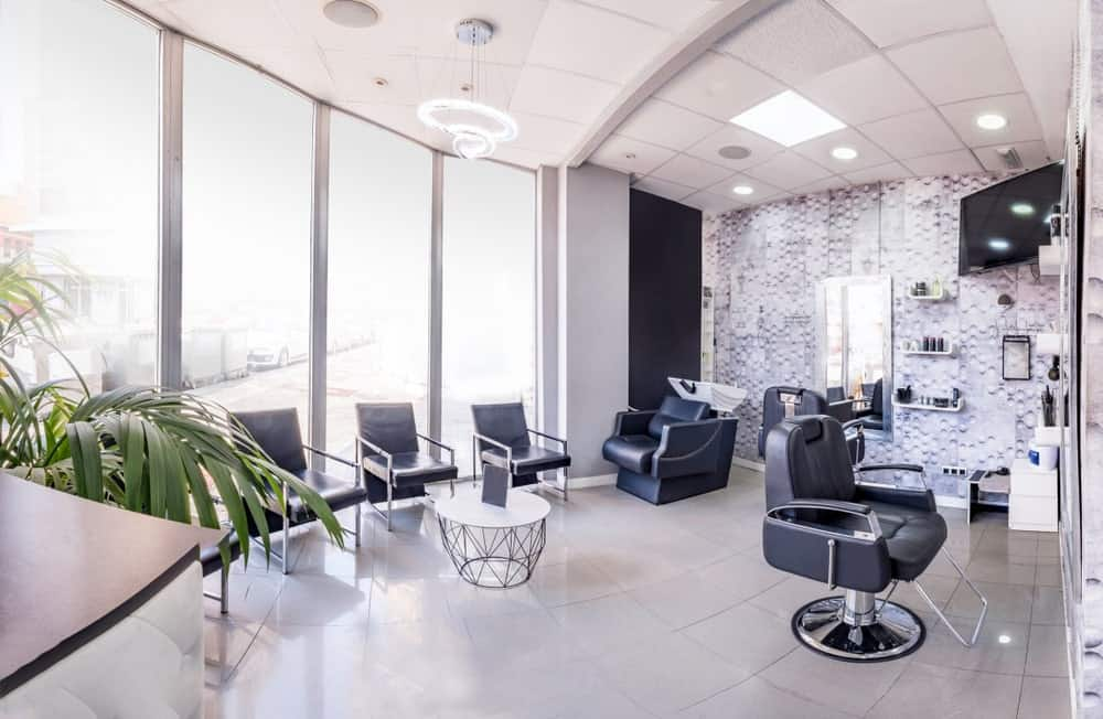 A bright and airy modern hair salon with rows of glass walls for a bright vibe.