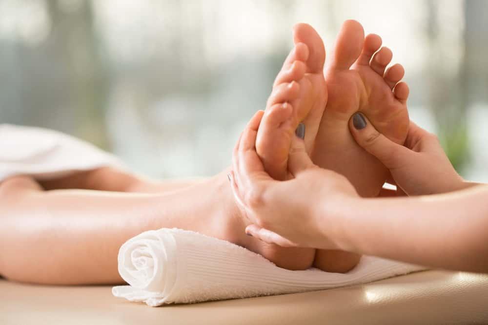 A woman having a reflexology foot massage.