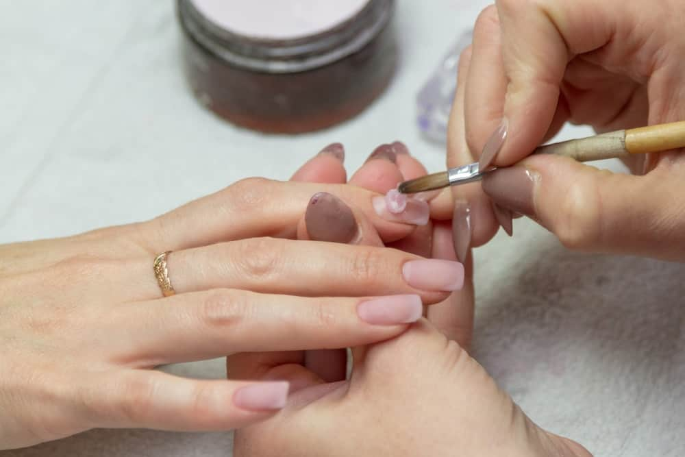 A woman having manicure at the salon with acrylic nails.