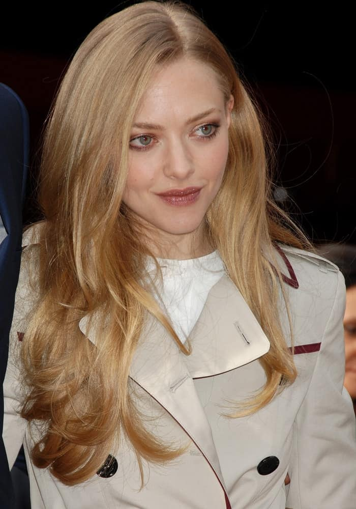 Amanda Seyfried was in attendance at the Hugh Jackman Star On The Hollywood Walk Of Fame Ceremony on December 13, 2012, in Los Angeles, CA. She wore a trench coat that she paired with her loose and tousled sandy blond hairstyle with subtle layers and highlights.