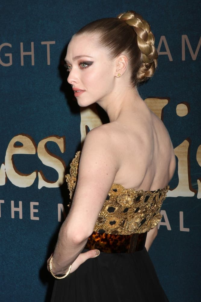"""Amanda Seyfried was quite stunning in the golden detailed dress that she paired with bold make-up and a high bun hairstyle incorporated with braids at the premiere of """"Les Miserables"""" at the Ziegfeld Theatre on December 10, 2012, in New York City."""