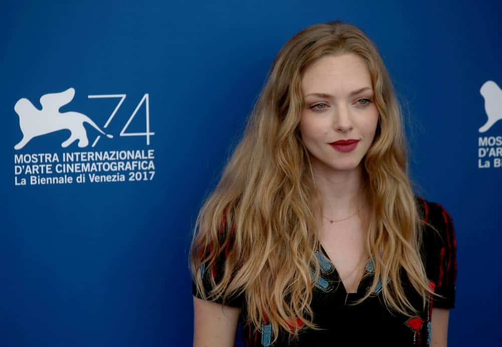 On August 31, 2017, Amanda Seyfried wore a casual black dress that she paired with her long sandy blond hair that was loose and tousled with subtle waves at the 'First Reformed' photocall during the 74th Venice Film Festival in Venice, Italy.