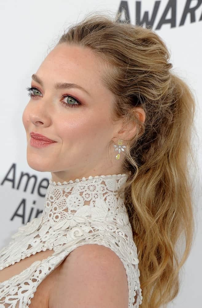 Amanda Seyfried paired her white embroidered outfit with a charming messy tousled ponytail hairstyle with highlighted and wavy tips at the 2018 Film Independent Spirit Awards held at Santa Monica Beach, USA on March 3, 2018.