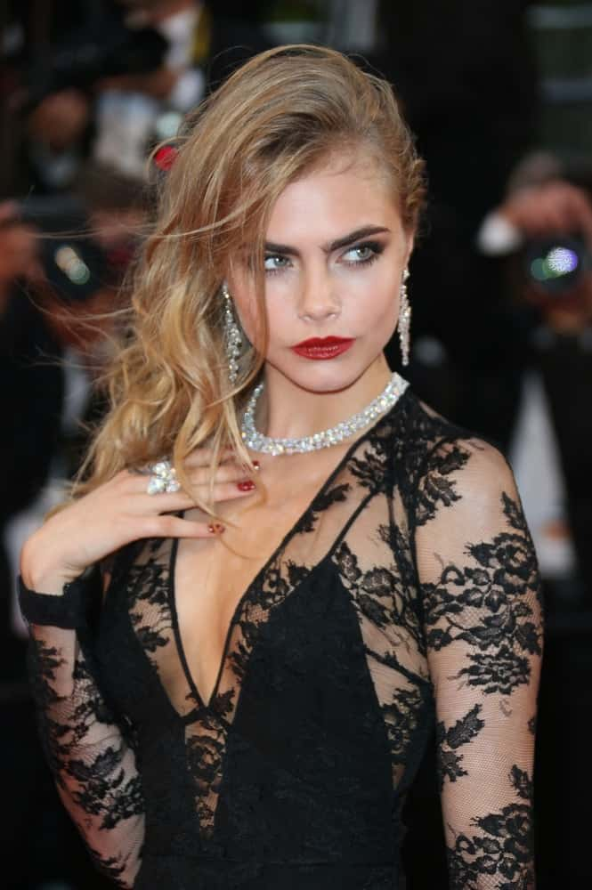 On May 15, 2013, Cara Delevingne was quite sexy in her black sheer dress, red lipstick and tousled side-swept hairstyle with a wet-look finish to its highlighted waves at the 66th Cannes Film Festival – Opening ceremony and Great Gatsby premiere, Cannes, France.