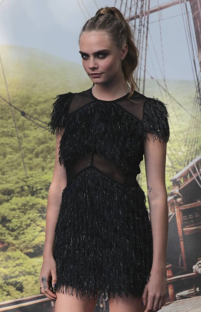 """Cara Delevingne's short vintage black dress was complemented by her simple high ponytail hairstyle incorporated with braids when she attended the """"Pan"""" film premiere on Sep 20, 2015, in London."""