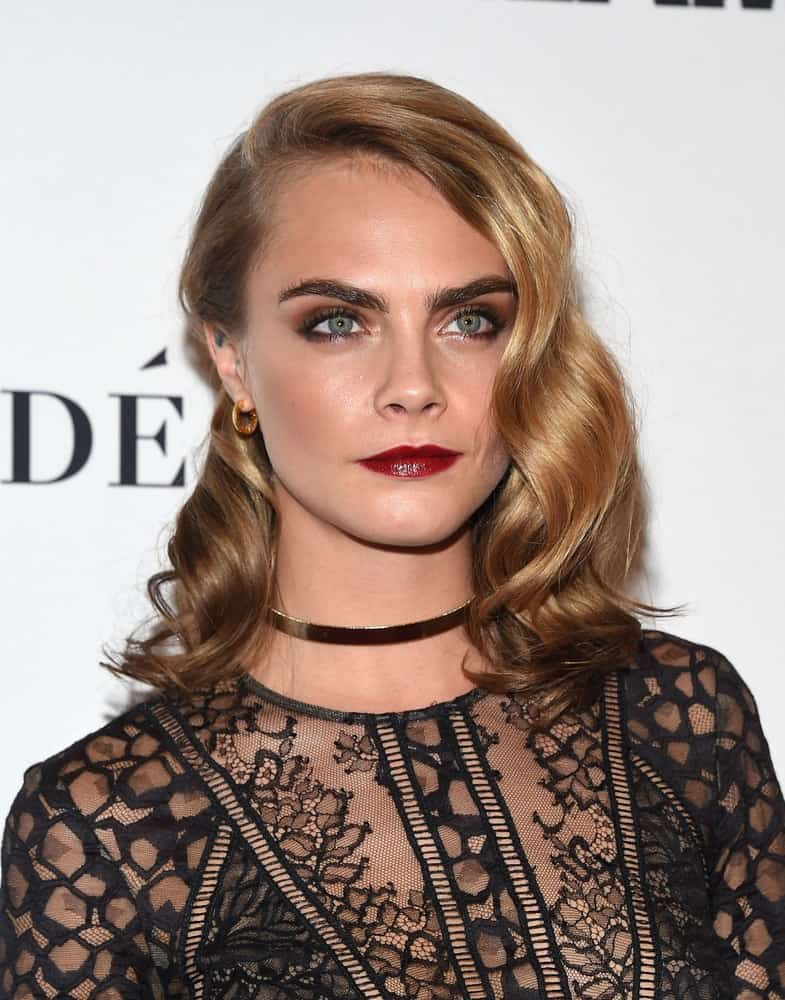 Cara Delevingne flaunted her famous eyebrows with her black sheer outfit and side-swept sandy blond hairstyle incorporated with vintage curls at the Glamour Celebrates Women of the Year Awards 2016 on November 14, 2016, in Hollywood, CA.