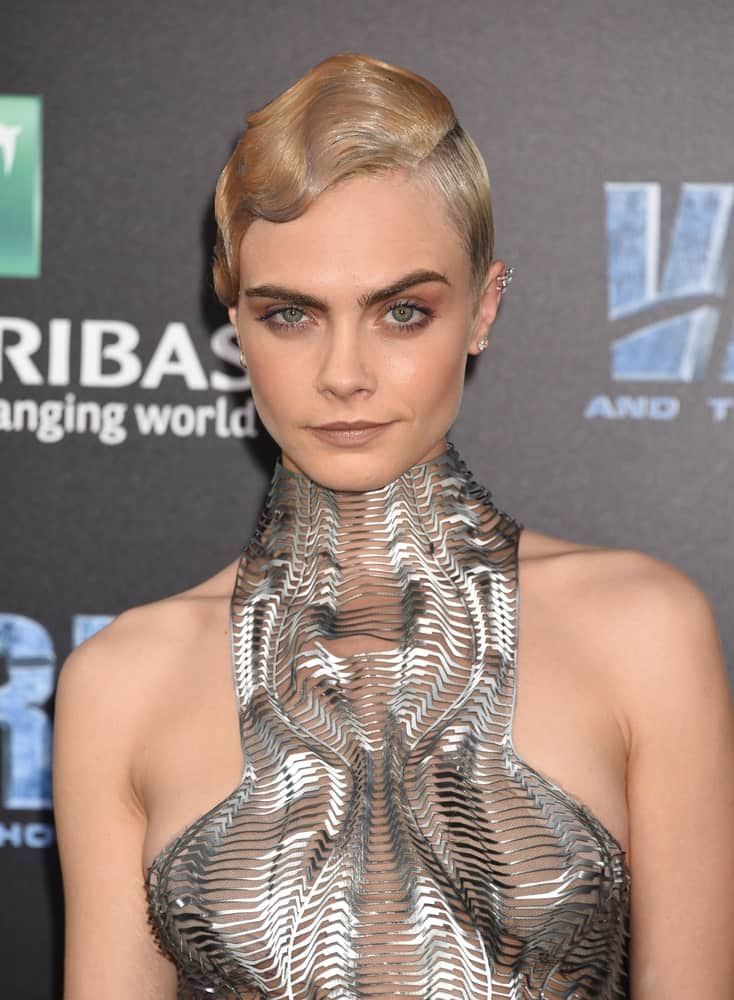 "Cara Delevingne attended the ""Valerian And The City Of A Thousand Planets"" World Premiere on July 17, 2017, in Hollywood, CA. She was quite fashionable in the metallic futuristic dress that she paired with a slick side-parted bun hairstyle with a sandy blond tone."