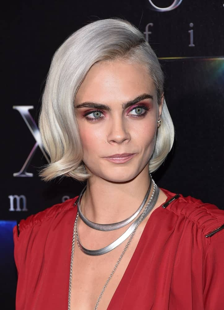 Cara Delevingne wore a charming red dress to match with her platinum blond chin-length hairstyle with a flippy finish and side-swept bangs at the CinemaCon 2017-STX Films