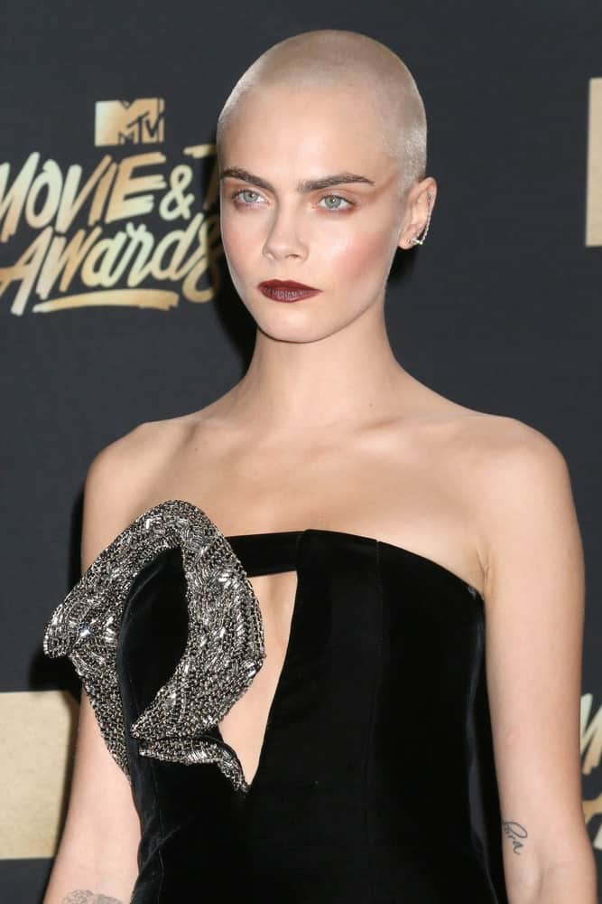 Cara Delevingne went with an edgy platinum blond buzz cut to go with her bold make-up and black dress at the MTV Movie and Television Awards on the Shrine Auditorium on May 7, 2017, in Los Angeles, CA.