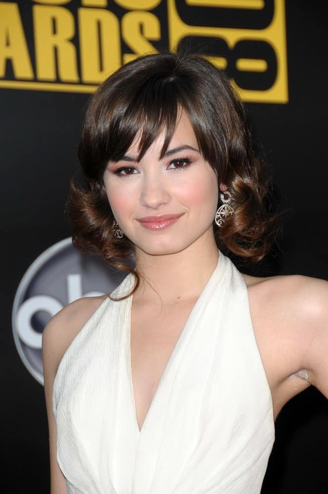 Demi Lovato wore a white dress with her curly shoulder-length hairstyle with highlights and bangs at the 2008 American Music Awards held at the Nokia Theatre in Los Angeles, CA on November 23, 2008.
