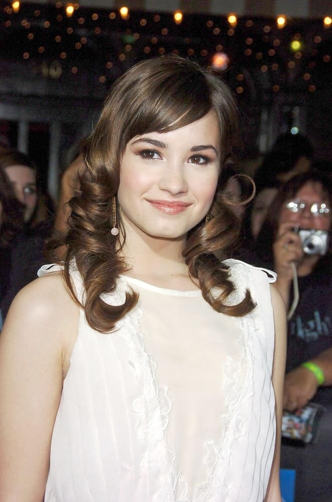 The young actress Demi Lovato was at the TWILIGHT Premiere held at the Mann Village and Bruin Theaters in Los Angeles, CA on November 17, 2008. She wore a simple white dress with her medium-length curly highlighted hairstyle with bangs.