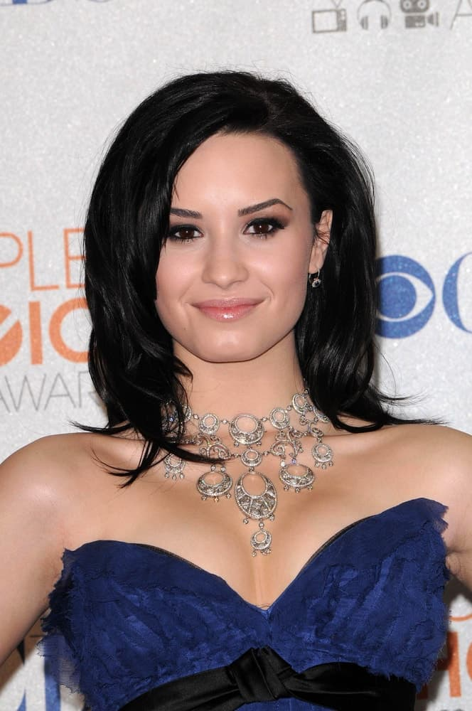 Demi Lovato's lovely blue strapless dress paired quite well with her raven shoulder-length hairstyle that has layers and side-swept bangs at the 2010 People's Choice Awards Press Room, Nokia Theater L.A. Live in Los Angeles, CA on January 6, 2010.