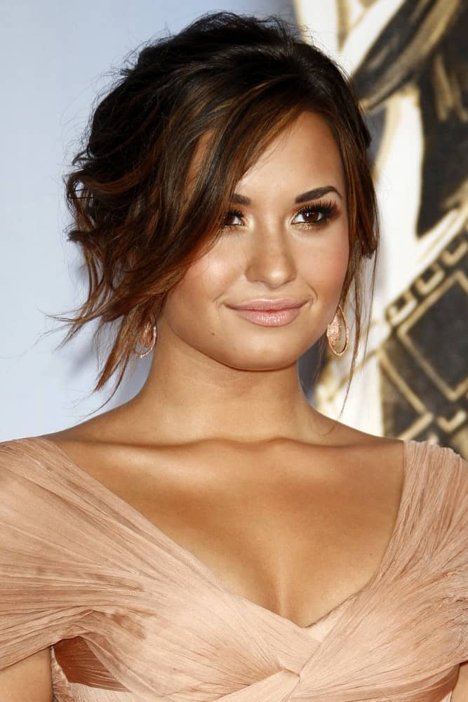 Demi Lovato wowed everyone with her simple make-up and messy bun hairstyle with loose highlighted side-swept bangs at the 2011 NCLR ALMA Awards held at Santa Monica Civic Auditorium on September 10, 2011, in Santa Monica, CA.