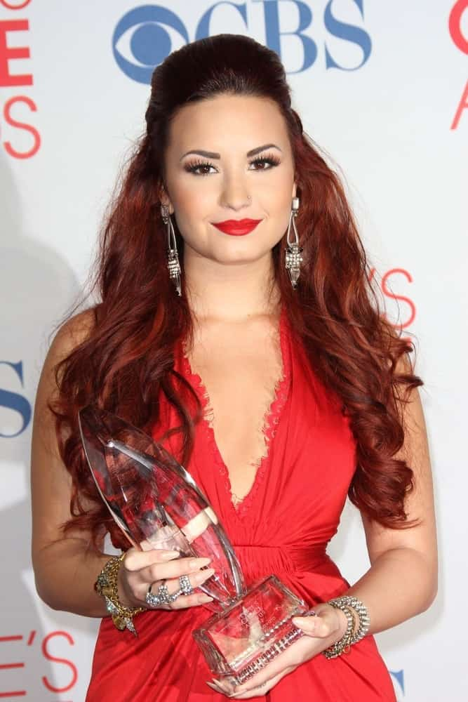 Demi Lovato was quite stunning with her red dress, red lips and red-dyed hairstyle in a half-up tousled hairstyle with waves and curls at the 2012 People's Choice Awards Press Room, Nokia Theatre in Los Angeles, CA on January 11, 2012.