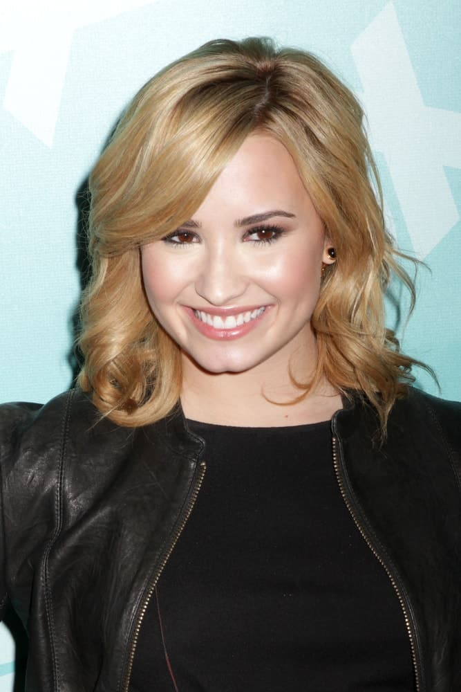 Demi Lovato wore a black outfit and leather jacket with her blond shoulder-length curls with long side-swept bangs and highlights when she attended the 2013 Fox Upfront at Wollman Rink on May 13, 2013, in New York City.