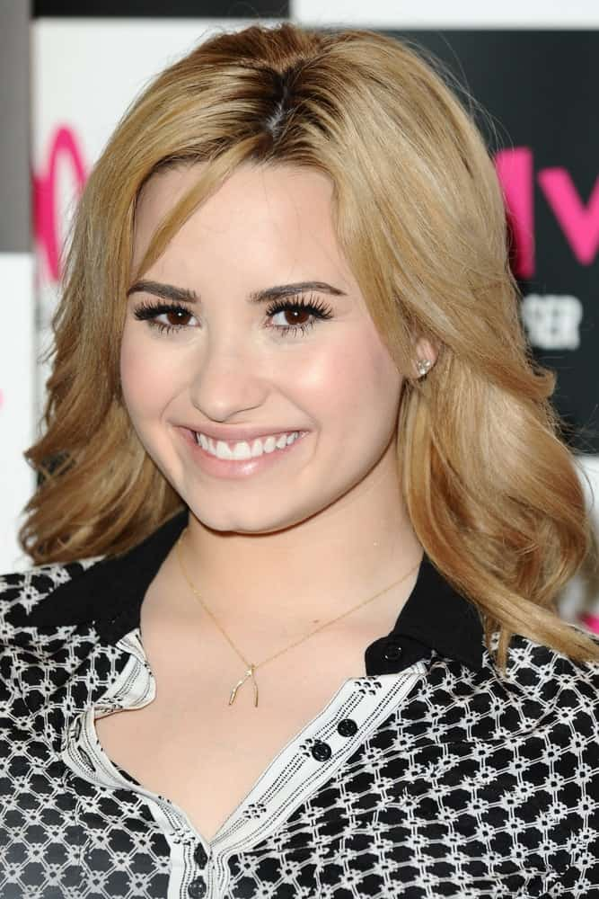 """Demi Lovato signed copies of her new album """"Unbroken"""" at the HMV Oxford Street in London on May 28, 2013. She was quite charming in her black outfit that complimented her shoulder-length blond curls with layers and highlights."""
