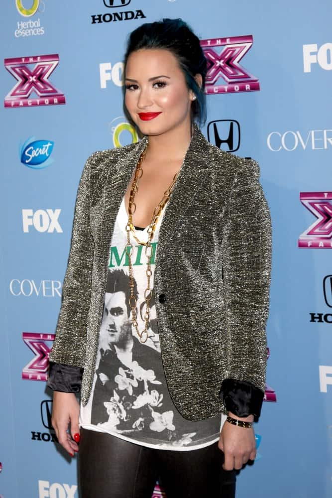 "Demi Lovato's smart casual outfit paired quite well with her blue-toned dark hairstyle that was swept up for a bun hairstyle that has loose tendrils on the side at the 2013 ""X Factor"" Top 12 Party at the SLS Hotel on November 4, 2013, in Beverly Hills, CA."