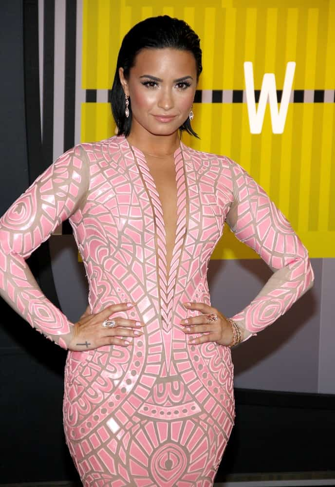 Demi Lovato paired her gorgeous pink patterned fit dress with her raven slicked back short hairstyle and confident smile at the 2015 MTV Video Music Awards held at the Microsoft Theater in Los Angeles, USA on August 30, 2015.