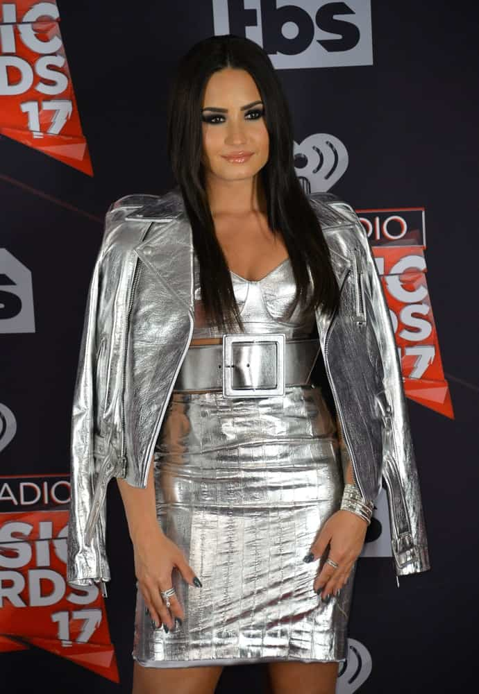 On March 5, 2017, Demi Lovato wore a fashionable and stylish silver dress with a matching jacket to pair with her long and straight hairstyle with layers at the 2017 iHeartRadio Music Awards at The Forum in Los Angeles.
