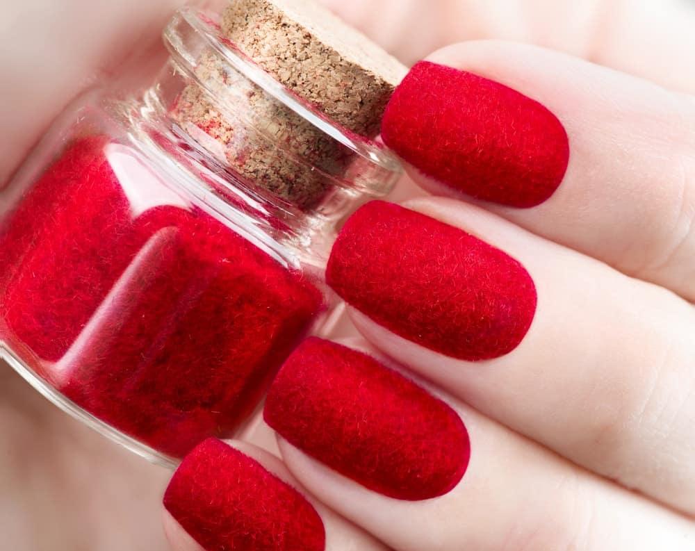 A close-up of trendy red velvet nails holding a bottle of red velvet polish.