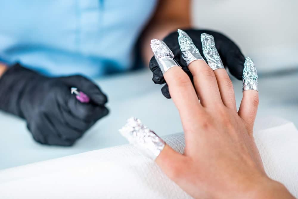 A woman having her nails done in a salon with soak off gel.