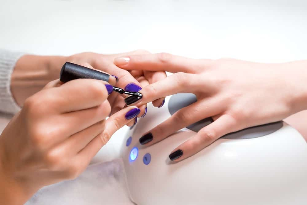 A manicurist applying nail gel polish on a client.