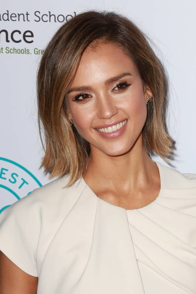 Jessica Alba wore a lovely beige dress to pair with her short tousled and highlighted hairstyle that has side-swept bangs at the 2015 Impact Awards Dinner at the Beverly Wilshire Hotel on March 17, 2015, in Beverly Hills, CA.