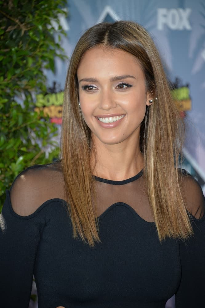 On July 31, 2016, Actress Jessica Alba wore a simple yet charming black dress with her medium-length and straight brown hairstyle that is loose and highlighted at the 2016 Teen Choice Awards at The Forum in Inglewood, California.